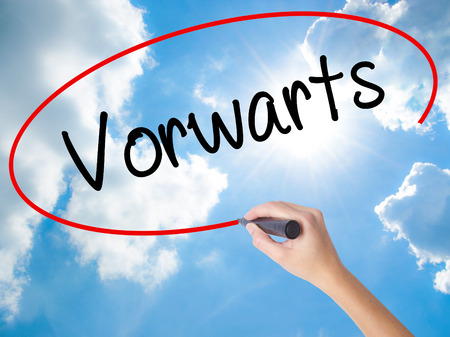 Woman Hand Writing Vorwarts  (Forward In German)  with black marker on visual screen. Isolated on Sunny Sky. Business concept. Stock Photo