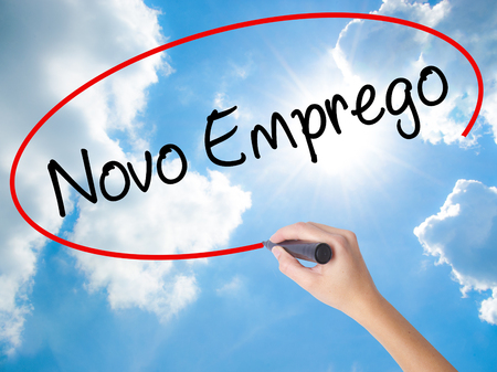 Woman Hand Writing  Novo Emprego (New Job in Portuguese)   with black marker on visual screen. Isolated on Sunny Sky. Business concept. Stock Photo Stock Photo