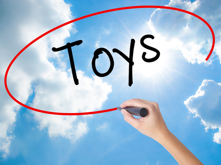 Woman Hand Writing Toys  with black marker on visual screen. Isolated on Sunny Sky. Business concept. Stock Photo