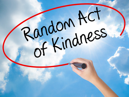 Woman Hand Writing Random Act of Kindness with black marker on visual screen. Isolated on Sunny Sky. Business concept. Stock Photo