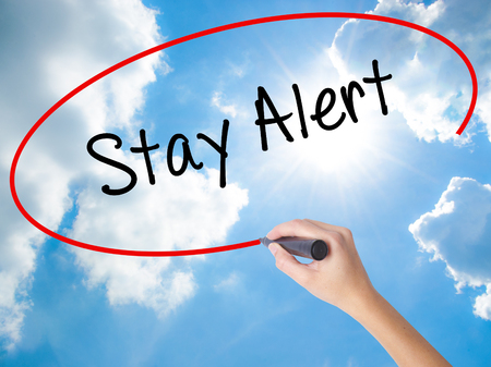 Woman Hand Writing Stay Alert with black marker on visual screen. Isolated on Sunny Sky. Business concept. Stock Photo