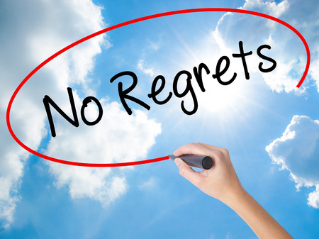 Woman Hand Writing No Regrets with black marker on visual screen. Isolated on Sunny Sky. Business concept. Stock Photo