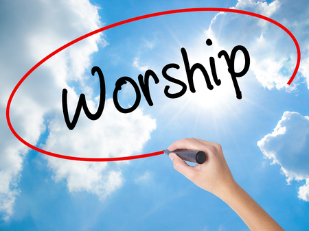 worshipper: Woman Hand Writing Worship with black marker on visual screen. Isolated on Sunny Sky. Business concept. Stock Photo