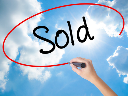 Woman Hand Writing Sold with black marker on visual screen. Isolated on Sunny Sky. Business concept. Stock Photo