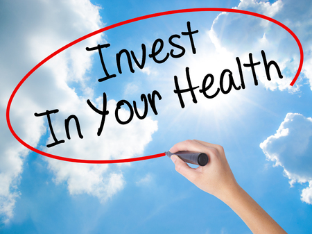 Woman Hand Writing Invest In Your Health with black marker on visual screen. Isolated on Sunny Sky. Business concept. Stock Photo Stock Photo