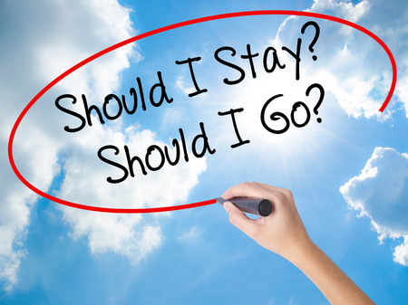 Woman Hand Writing Should I Stay? Should I Go? with black marker on visual screen. Isolated on Sunny Sky. Business concept. Stock Photo Stock Photo