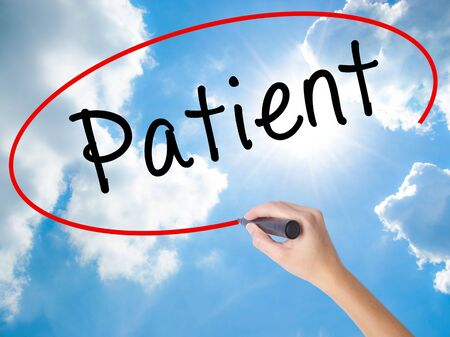 immediate: Woman Hand Writing Patient with black marker on visual screen. Isolated on Sunny Sky. Business concept. Stock Photo