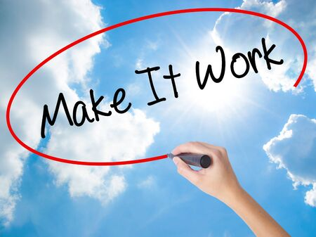 Woman Hand Writing Make It Work with black marker on visual screen. Isolated on Sunny Sky. Business concept. Stock Photo