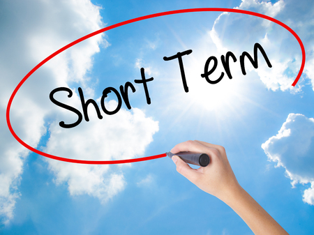 Woman Hand Writing Short Term with black marker on visual screen. Isolated on Sunny Sky. Business concept. Stock Photo Stock Photo