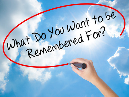 Woman Hand Writing What Do You Want to be Remembered For? with black marker on visual screen. Isolated on Sunny Sky. Business concept. Stock Photo