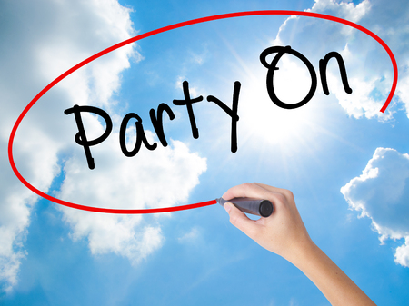 Woman Hand Writing Party On with black marker on visual screen. Isolated on Sunny Sky. Business concept. Stock Photo