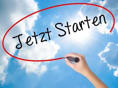 Woman Hand Writing Jetzt Starten (Start Now in German) with black marker on visual screen. Isolated on Sunny Sky. Business, technology, internet concept.