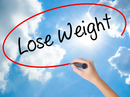Woman Hand Writing Lose Weight with black marker on visual screen. Isolated on Sunny Sky. Business concept. Stock Photo