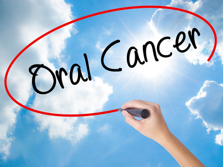 Woman Hand Writing Oral Cancer  with black marker on visual screen. Isolated on Sunny Sky. Business concept. Stock Photo Stock Photo