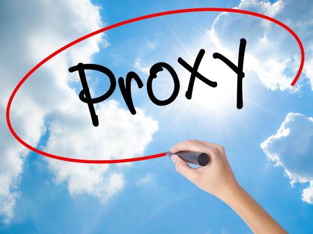 Woman Hand Writing Proxy with black marker on visual screen. Isolated on Sunny Sky. Business concept. Stock Photo
