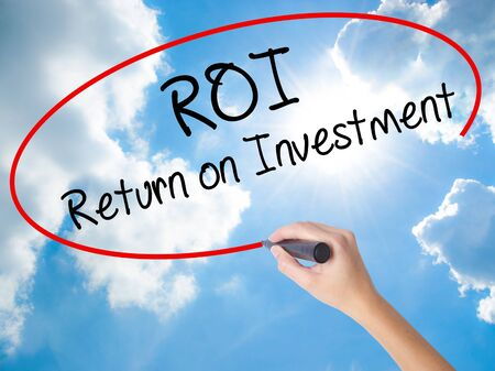 Woman Hand Writing ROI  Return on Investment with black marker on visual screen. Isolated on Sunny Sky. Business concept. Stock Photo