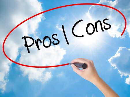Woman Hand Writing Pros  Cons with black marker on visual screen. Isolated on Sunny Sky. Business, technology, internet concept.