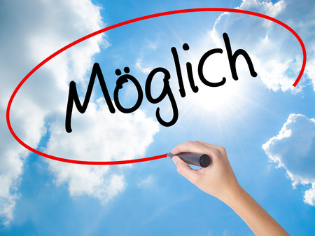 Woman Hand Writing Moglich (Possible in German) with black marker on visual screen. Isolated on Sunny Sky. Business concept. Stock Photo