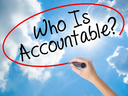 Woman Hand Writing Who Is Accountable? with black marker on visual screen. Isolated on Sunny Sky. Business concept. Stock Photo
