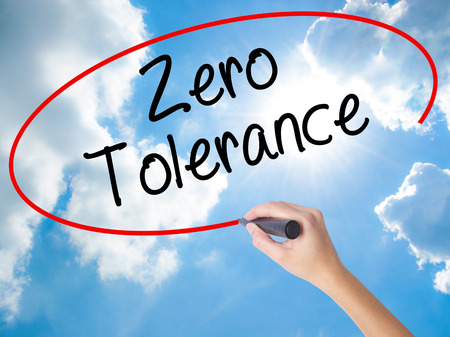 Woman Hand Writing Zero Tolerance with black marker on visual screen. Isolated on Sunny Sky. Business concept. Stock Photo Stock Photo