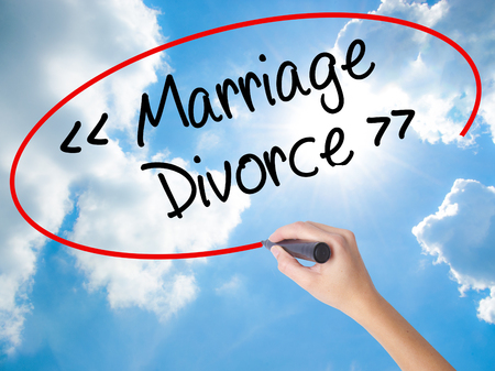 Woman Hand Writing Marriage - Divorce with black marker on visual screen. Isolated on Sunny Sky. Business concept. Stock Photo