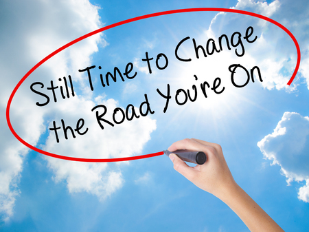 next horizon: Woman Hand Writing Still Time to Change the Road Youre On with black marker on visual screen. Isolated on Sunny Sky. Business concept. Stock Photo