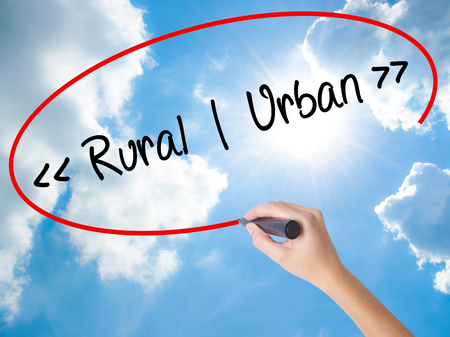 Woman Hand Writing Rural - Urban with black marker on visual screen. Isolated on Sunny Sky. Business concept. Stock Photo