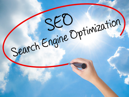 Woman Hand Writing SEO Search Engine Optimization with black marker on visual screen. Isolated on Sunny Sky. Business concept. Stock Photo