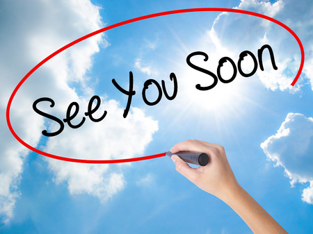 Woman Hand Writing See You Soon with black marker on visual screen. Isolated on Sunny Sky. Business concept. Stock Photo
