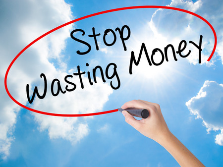 Woman Hand Writing Stop Wasting Money with black marker on visual screen. Isolated on Sunny Sky. Business concept. Stock Photo