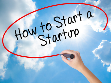 Woman Hand Writing How to Start a Startup with black marker on visual screen. Isolated on Sunny Sky. Business concept. Stock Photo