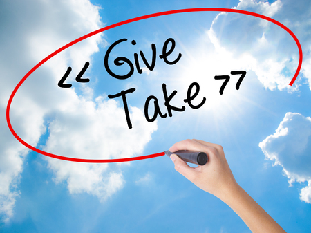 Woman Hand Writing Give - Take with black marker on visual screen. Isolated on Sunny Sky. Business concept. Stock Photo