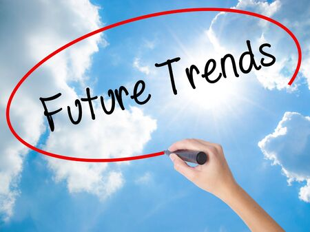 Woman Hand Writing Future Trends with black marker on visual screen. Isolated on Sunny Sky. Business, technology, internet concept. Stock Photo