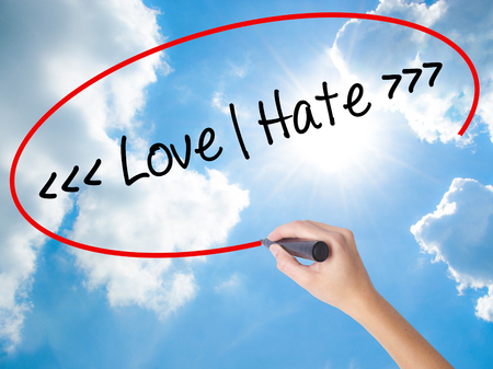 appraise: Woman Hand Writing Love - Hate  with black marker on visual screen. Isolated on Sunny Sky. Business concept. Stock Photo