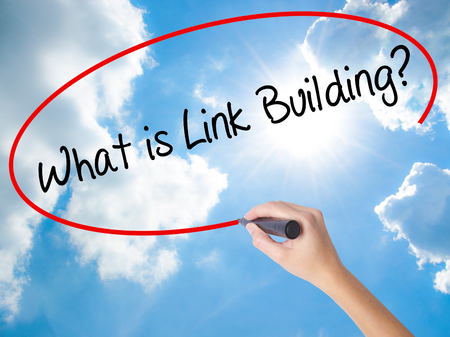 wiki: Woman Hand Writing What is Link Building? with black marker on visual screen. Isolated on Sunny Sky. Business concept. Stock Photo