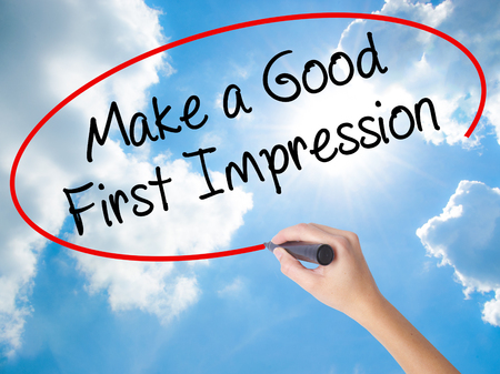 Woman Hand Writing Make a Good First Impression with black marker on visual screen. Isolated on Sunny Sky. Business concept. Stock Photo