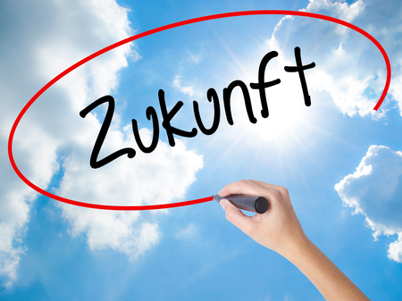 Woman Hand Writing Zukunft (Future in German)  with black marker on visual screen. Isolated on Sunny Sky. Business concept. Stock Photo