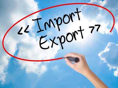 Woman Hand Writing Import - Export with black marker on visual screen. Isolated on Sunny Sky. Business concept. Stock Photo Stock Photo