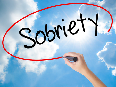 sobriety: Woman Hand Writing Sobriety with black marker on visual screen. Isolated on Sunny Sky. Business concept. Stock Photo Stock Photo