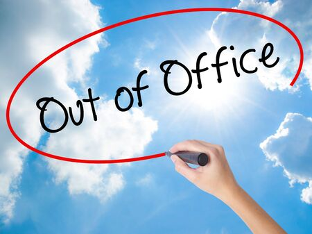Woman Hand Writing Out of Office with black marker on visual screen. Isolated on Sunny Sky. Business concept. Stock Photo