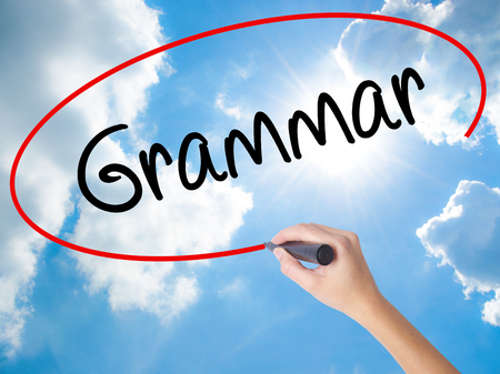 verb: Woman Hand Writing Grammar with black marker on visual screen. Isolated on Sunny Sky. Business concept. Stock Photo