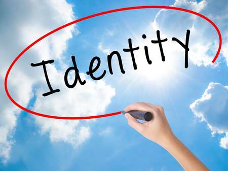 Woman Hand Writing Identity with black marker on visual screen. Isolated on Sunny Sky. Business concept. Stock Photo