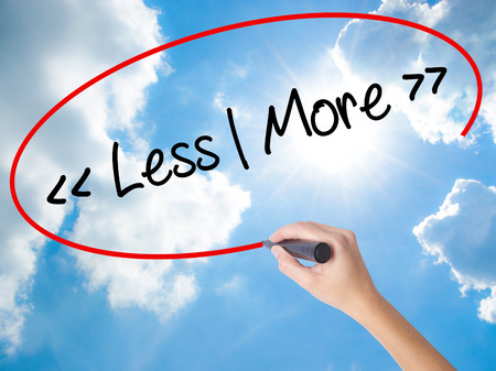 Woman Hand Writing Less - More with black marker on visual screen. Isolated on Sunny Sky. Business concept. Stock Photo