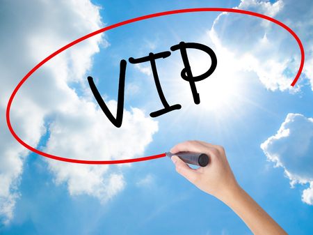 Woman Hand Writing  VIP with black marker on visual screen. Isolated on Sunny Sky. Business concept. Stock Photo