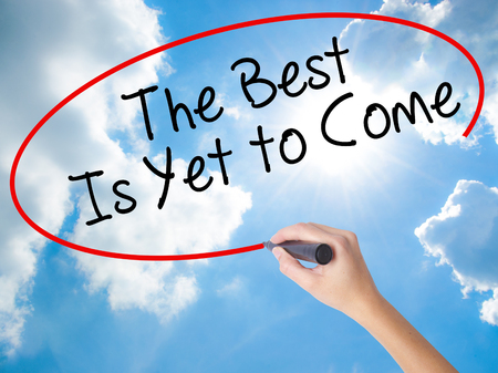 Woman Hand Writing The Best Is Yet to Come with black marker on visual screen. Isolated on Sunny Sky. Business concept. Stock Photo Stock Photo