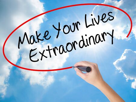 Woman Hand Writing Make Your Lives Extraordinary with black marker on visual screen. Isolated on Sunny Sky. Business concept. Stock Photo