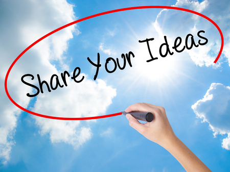Woman Hand Writing Share Your Ideas with black marker on visual screen. Isolated on Sunny Sky. Business concept. Stock Photo