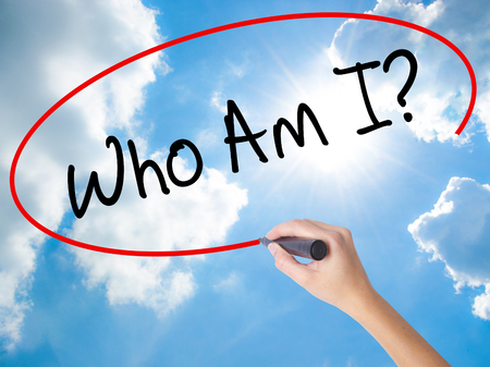 specification: Woman Hand Writing Who Am I? with black marker on visual screen. Isolated on Sunny Sky. Business concept. Stock Photo