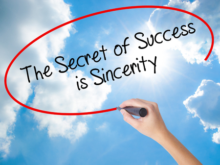 Woman Hand Writing The Secret of Success is Sincerity with black marker on visual screen. Isolated on Sunny Sky. Business concept. Stock Photo