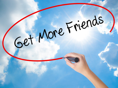 Woman Hand Writing Get More Friends with black marker on visual screen. Isolated on Sunny Sky. Business, technology, internet concept. Stock Photo